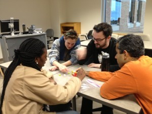picture of four students working together on a project at a table