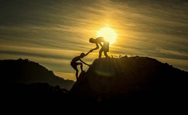 picture of a person giving a helping hand to another person on a mountain