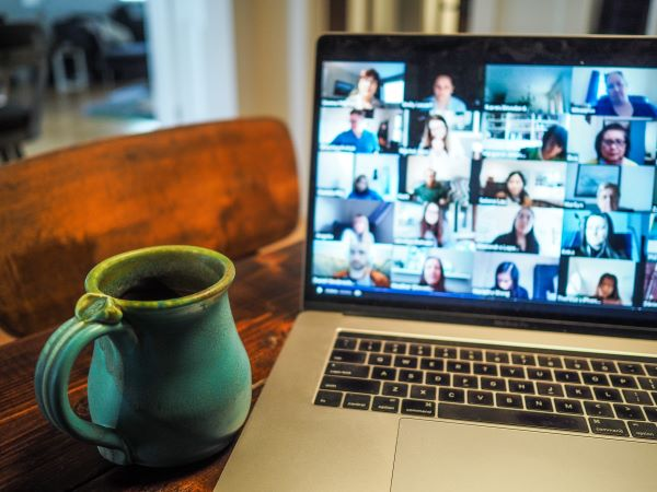 image of a laptop with a gallery view of a zoom meeting and cup of coffee next to computer