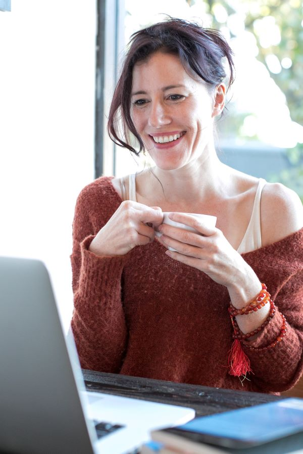 image of woman with a cup of coffee smiling in front of a computer screen