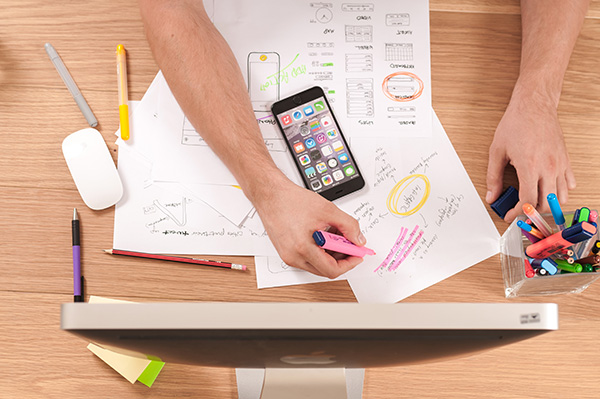 picture of highlighting papers, a phone, and a computer